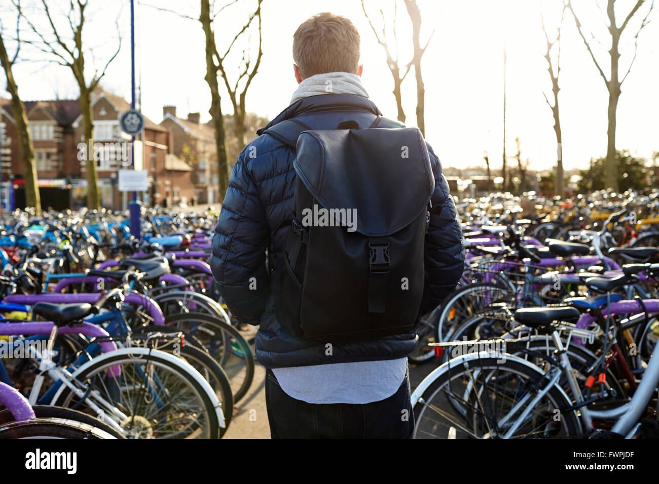 Vista trasera del hombre dejando en moto Cycle Park en la Estación de Tren Imagen De Stock