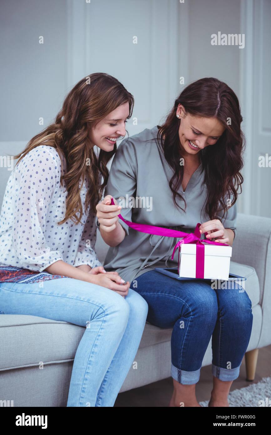 Amigos desenvolver un regalo en el salón Imagen De Stock