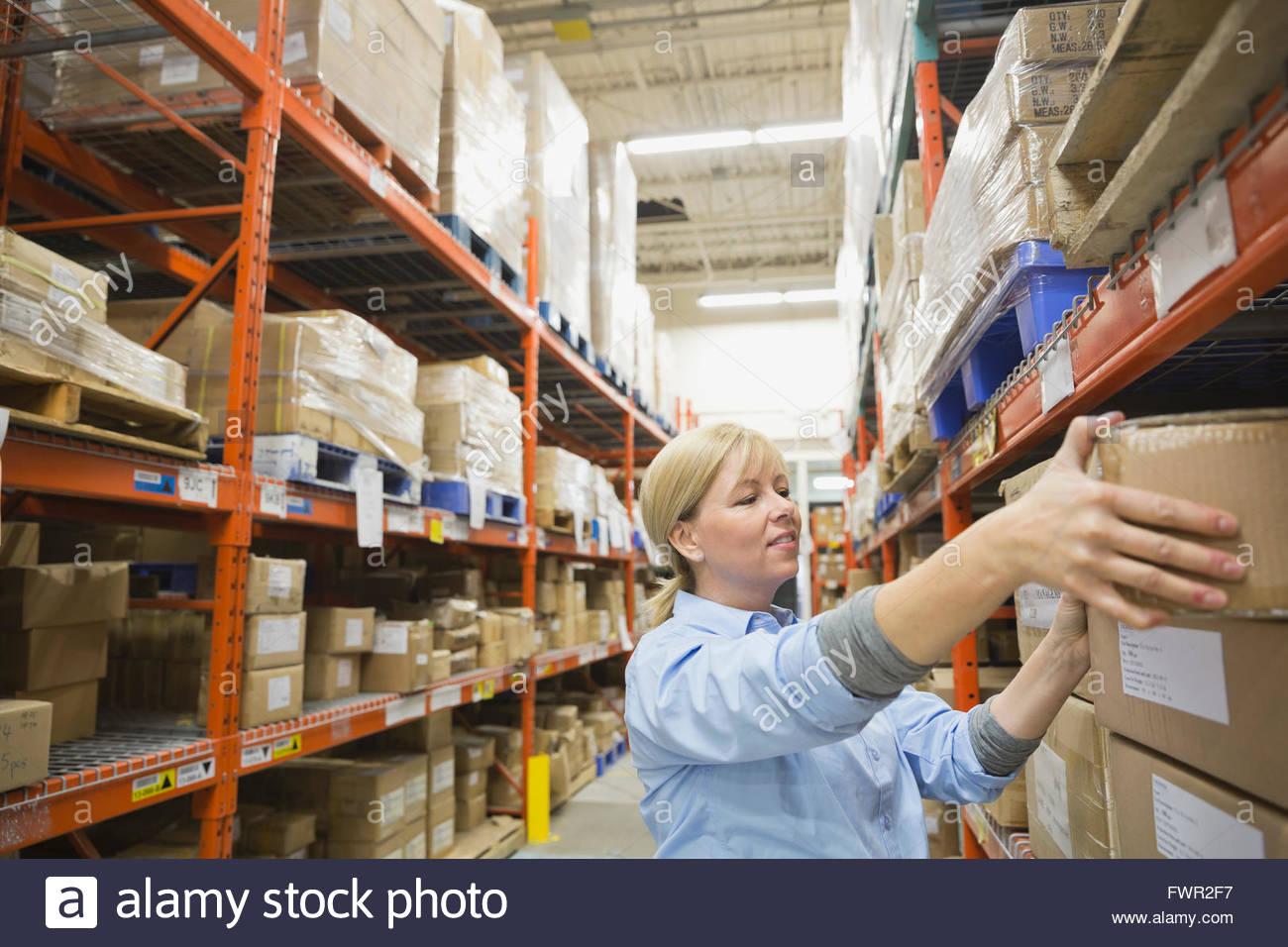 Trabajadora organizar existencias en almacén Imagen De Stock