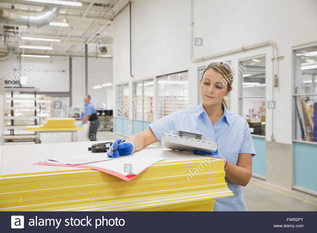 Trabajadora Revisar stock en la fábrica. Imagen De Stock