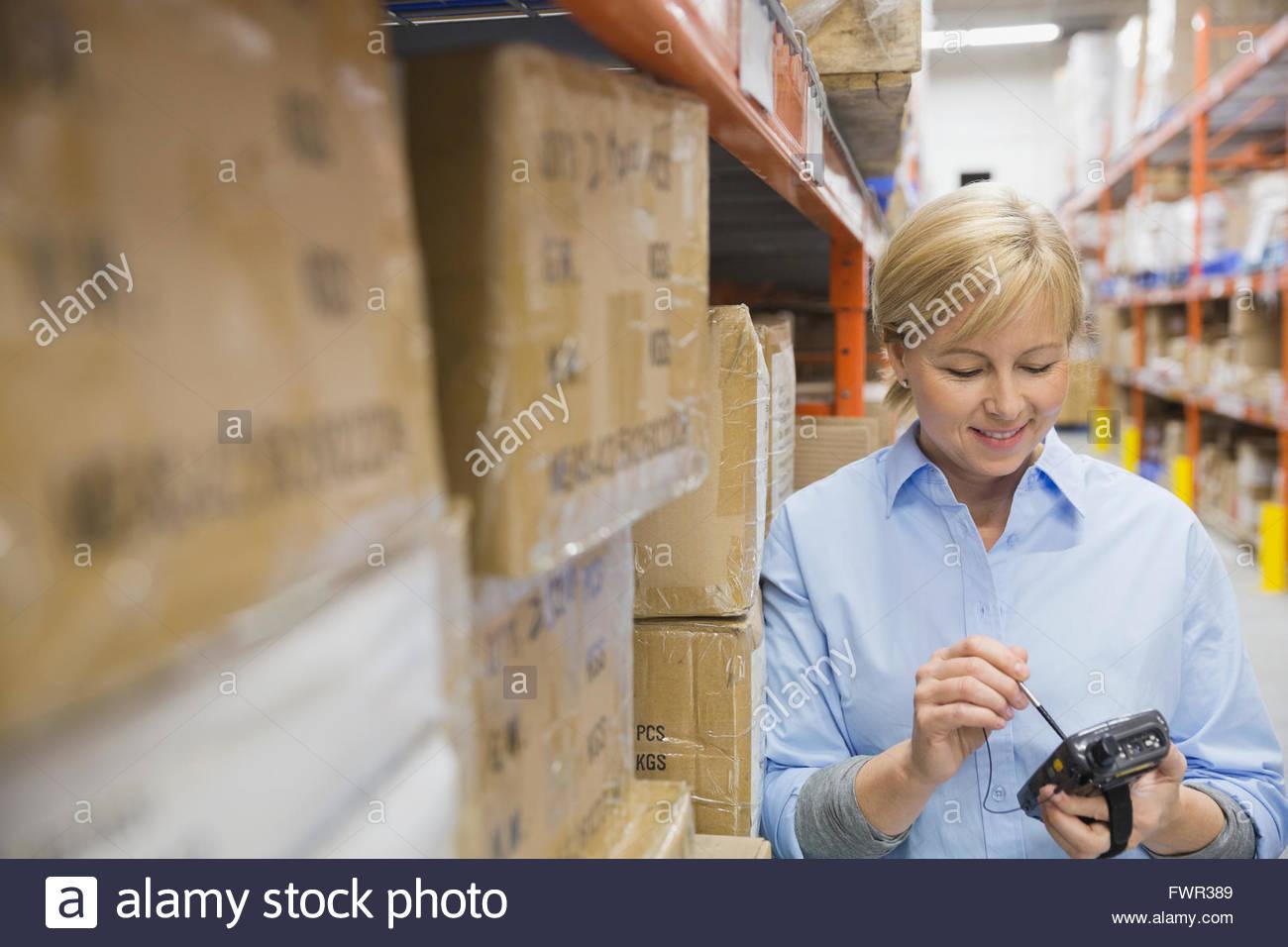 Trabajador de almacén mediante dispositivo de mano Imagen De Stock