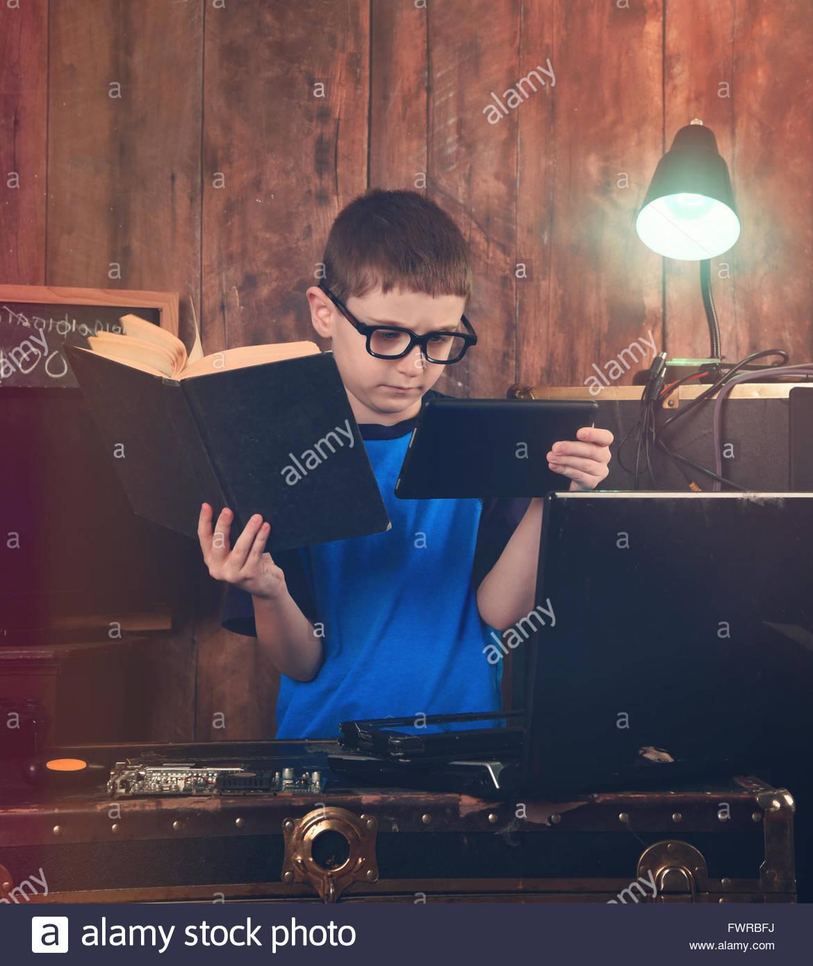Un niño está leyendo un libro de ciencia y la celebración de un internet tablet con objetos de equipo Imagen De Stock