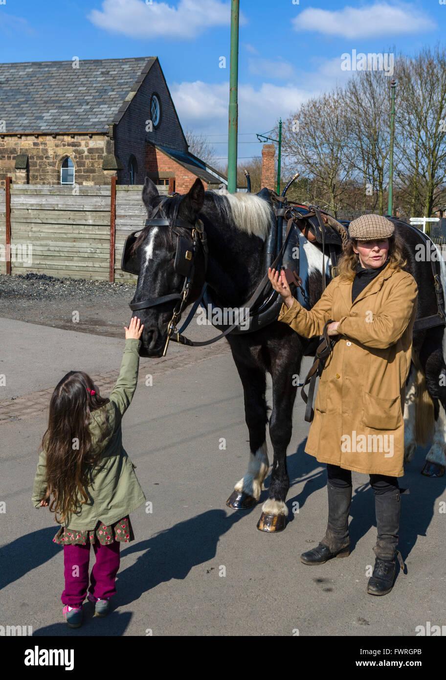 Niña de acariciar un caballo en el Black Country Living Museum, Dudley, West Midlands, Reino Unido Imagen De Stock