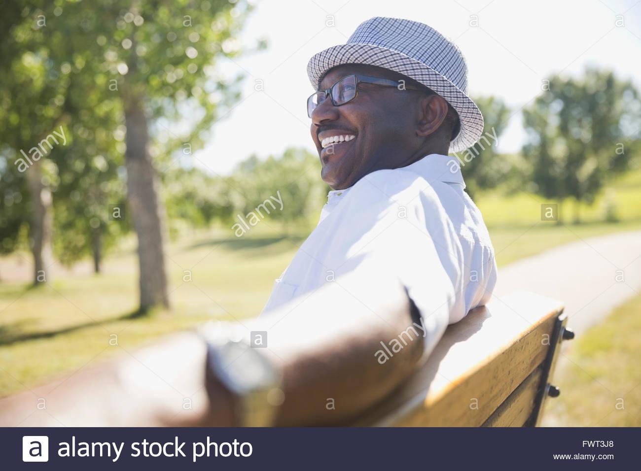 Senior sonriente hombre sentado en un banco del parque Imagen De Stock