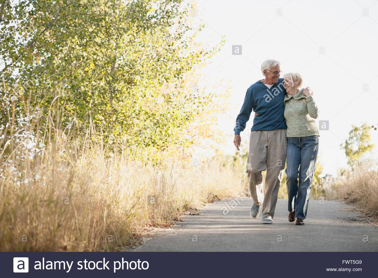 Feliz pareja senior caminando en el camino en el parque Imagen De Stock
