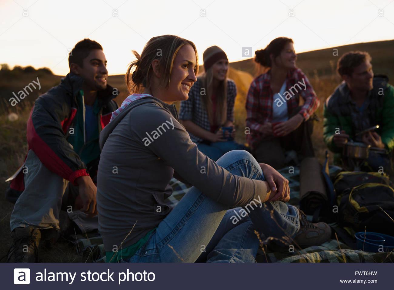 Amigos sentados al aire libre al atardecer. Imagen De Stock
