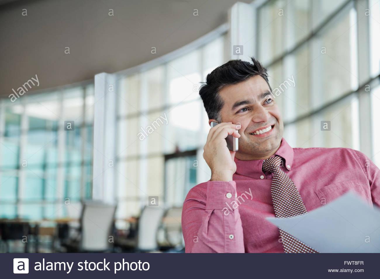 Empresario con documento contestando llamadas telefónicas Imagen De Stock