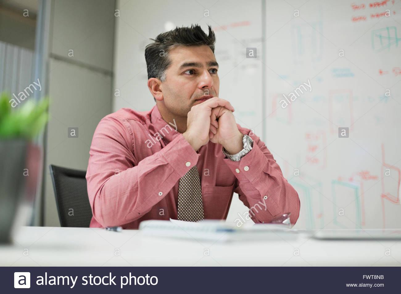 Empresario maduro sentado en el escritorio en la sala de la junta Imagen De Stock
