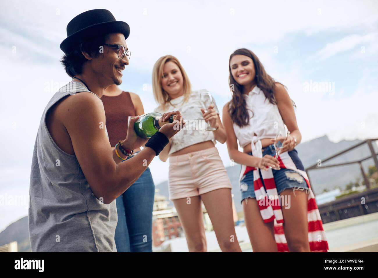 Disparó al aire libre de joven abrir una botella de champán con amigas de pie en el fondo de la piscina. Imagen De Stock