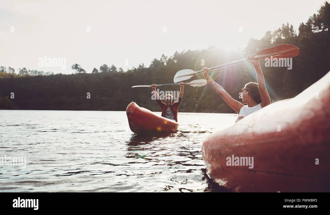 Feliz pareja de jóvenes disfrutando de canoa en el día de verano. Hombre y mujer joven divirtiéndose Imagen De Stock