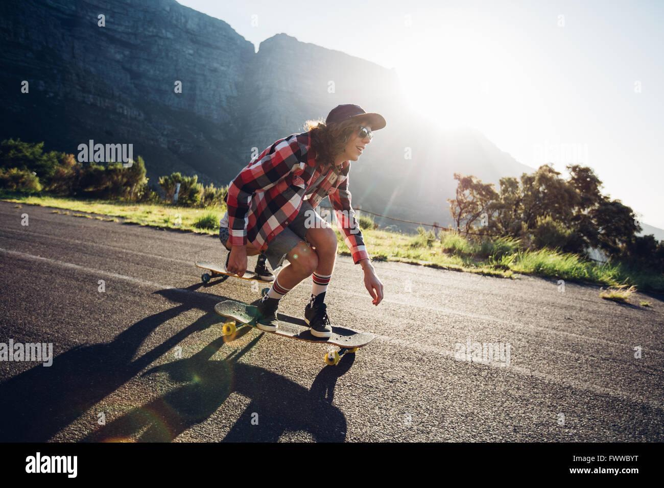 Joven longboarding afuera en carretera rural. Skateboarding macho en un día soleado. Imagen De Stock