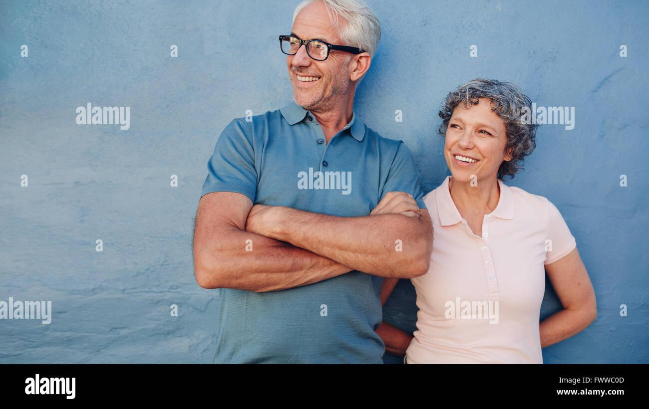 Retrato de una pareja de pie juntos y apartar la mirada y sonriendo contra el fondo azul. Un hombre y una mujer Foto de stock