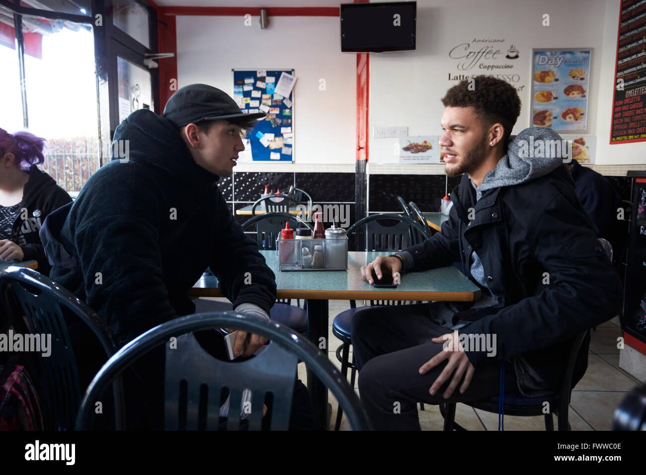 Dos estudiantes varones comiendo comida en el CaféFoto de stock