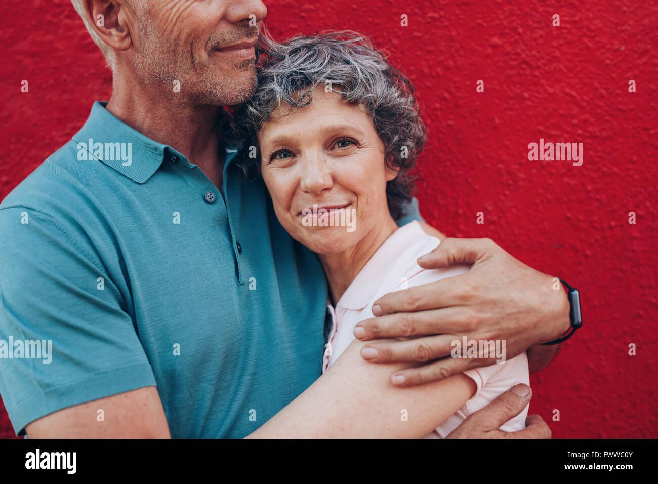 Retrato de mujer madura feliz abrazando a su marido contra el fondo rojo. Afectuoso par juntos contra el fondo rojo. Imagen De Stock