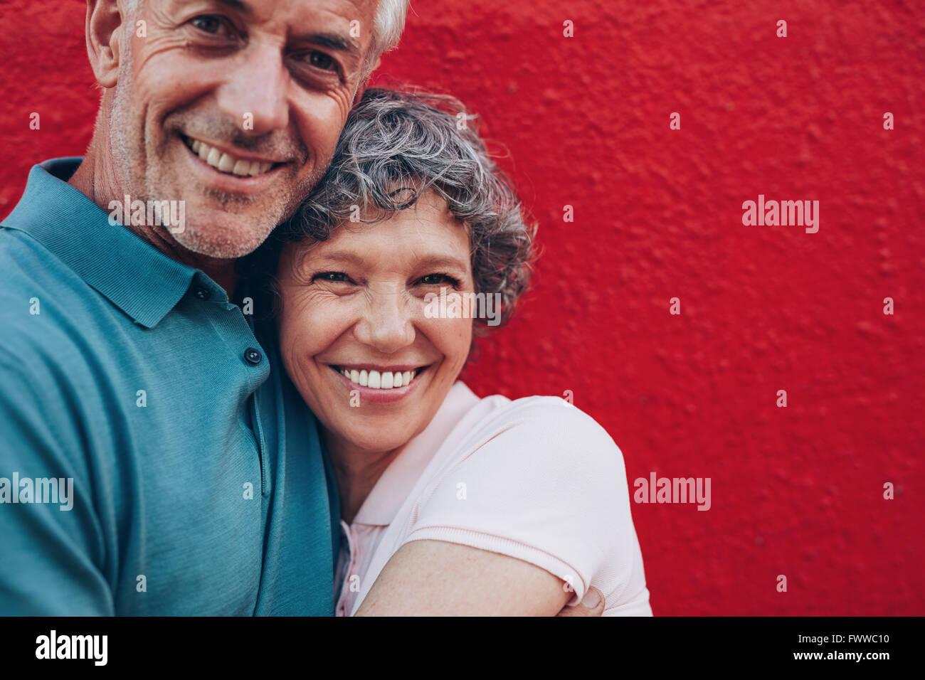 Retrato de la alegre pareja de mediana edad abrazándose entre sí contra el fondo rojo. Hombre y mujer Imagen De Stock
