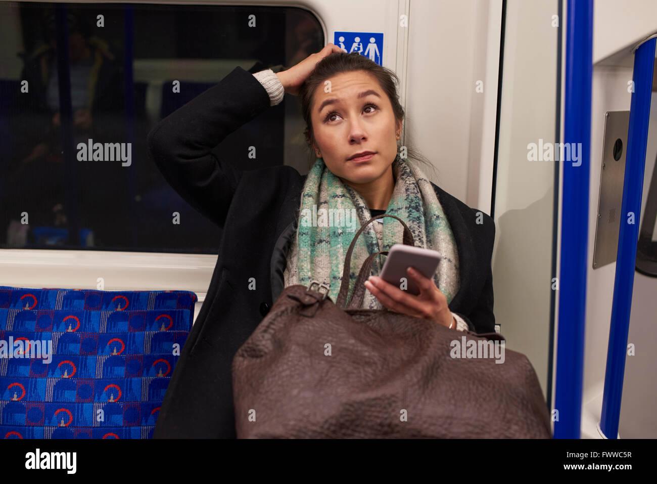 Mujer sentada en carro de Metro buscando en mensaje de texto Imagen De Stock