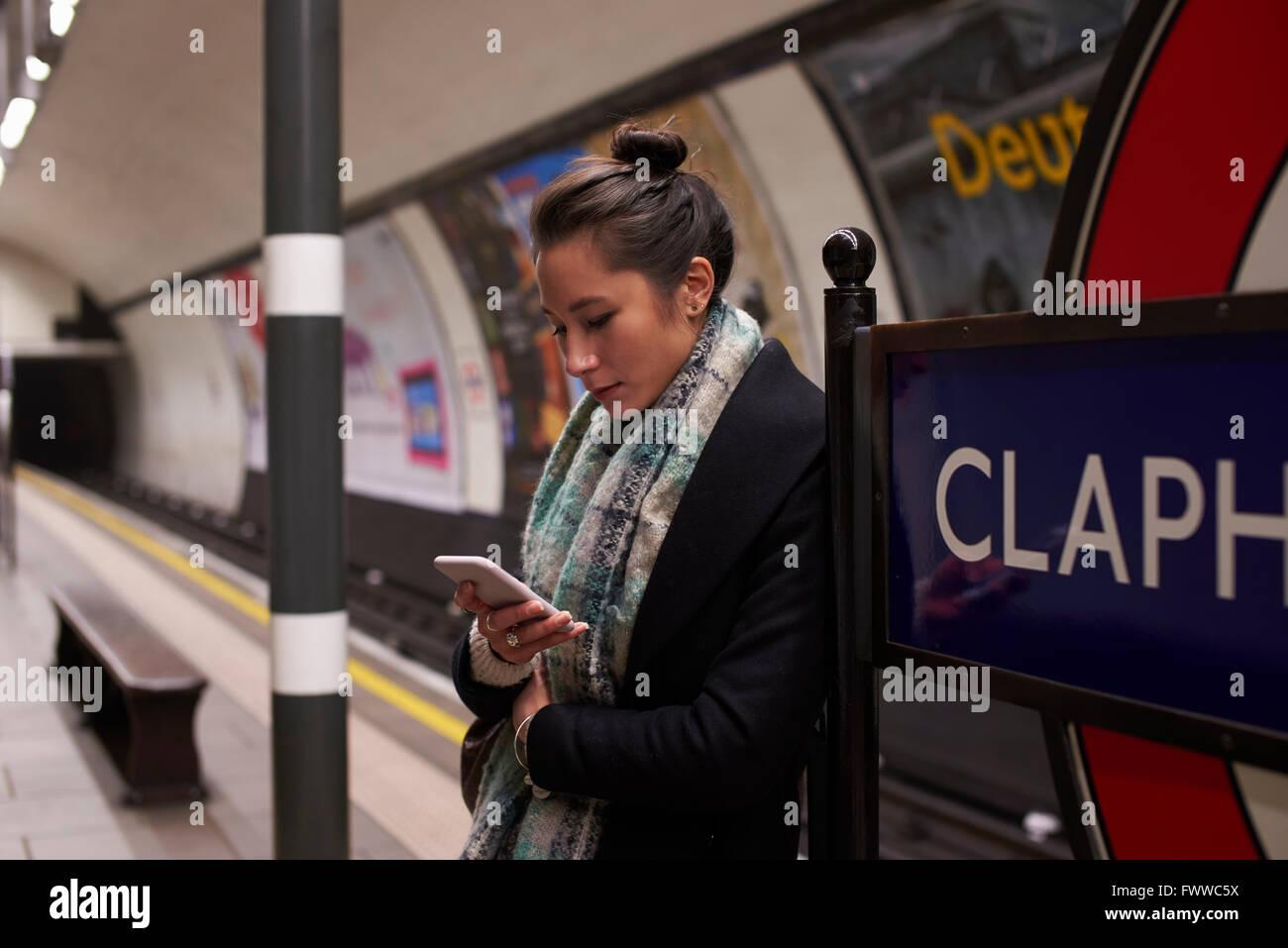 Mujer de pie sobre la plataforma mirando Metro en mensaje de texto Imagen De Stock