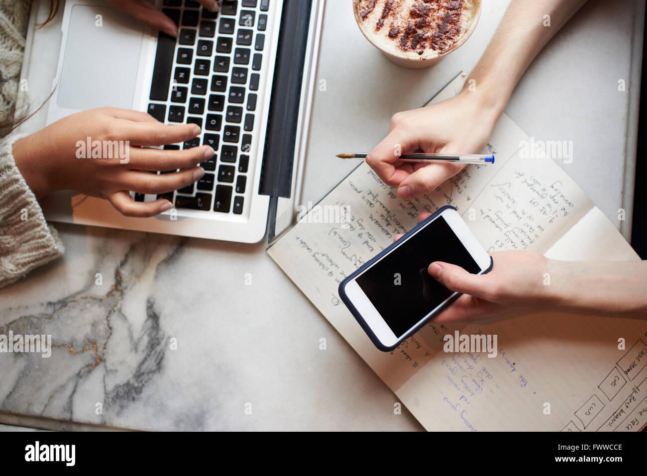 Cerca de dos personas que trabajan de forma remota en el Café Imagen De Stock