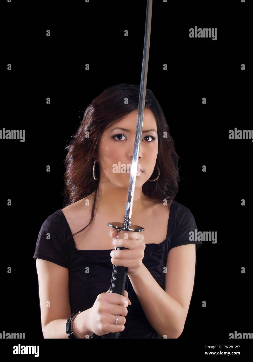 Joven Mujer Asiática sosteniendo la espada japonesa delante de la cara Foto de stock