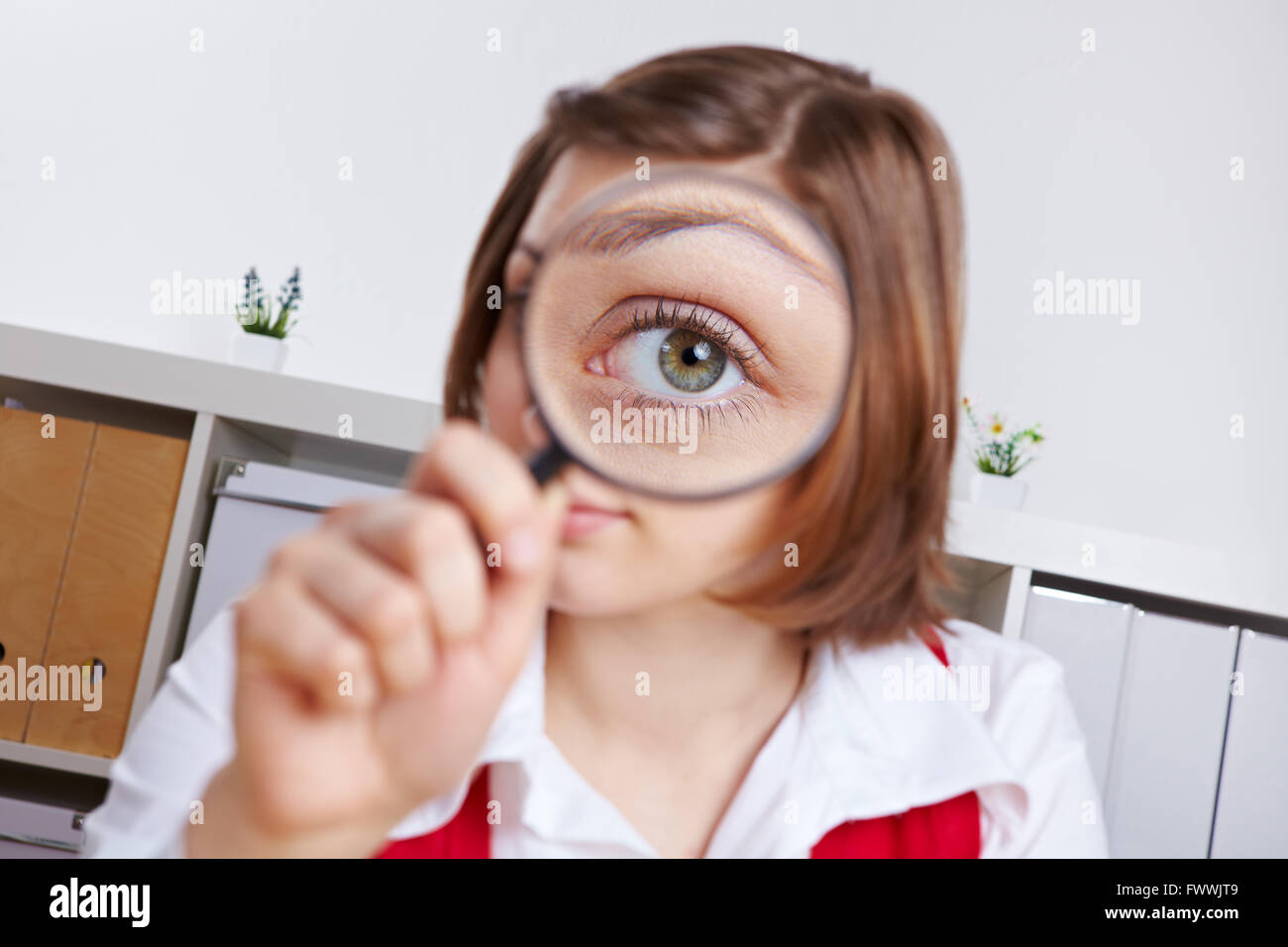 Mujer en la oficina mirando a través de una lupa con su ojo Imagen De Stock