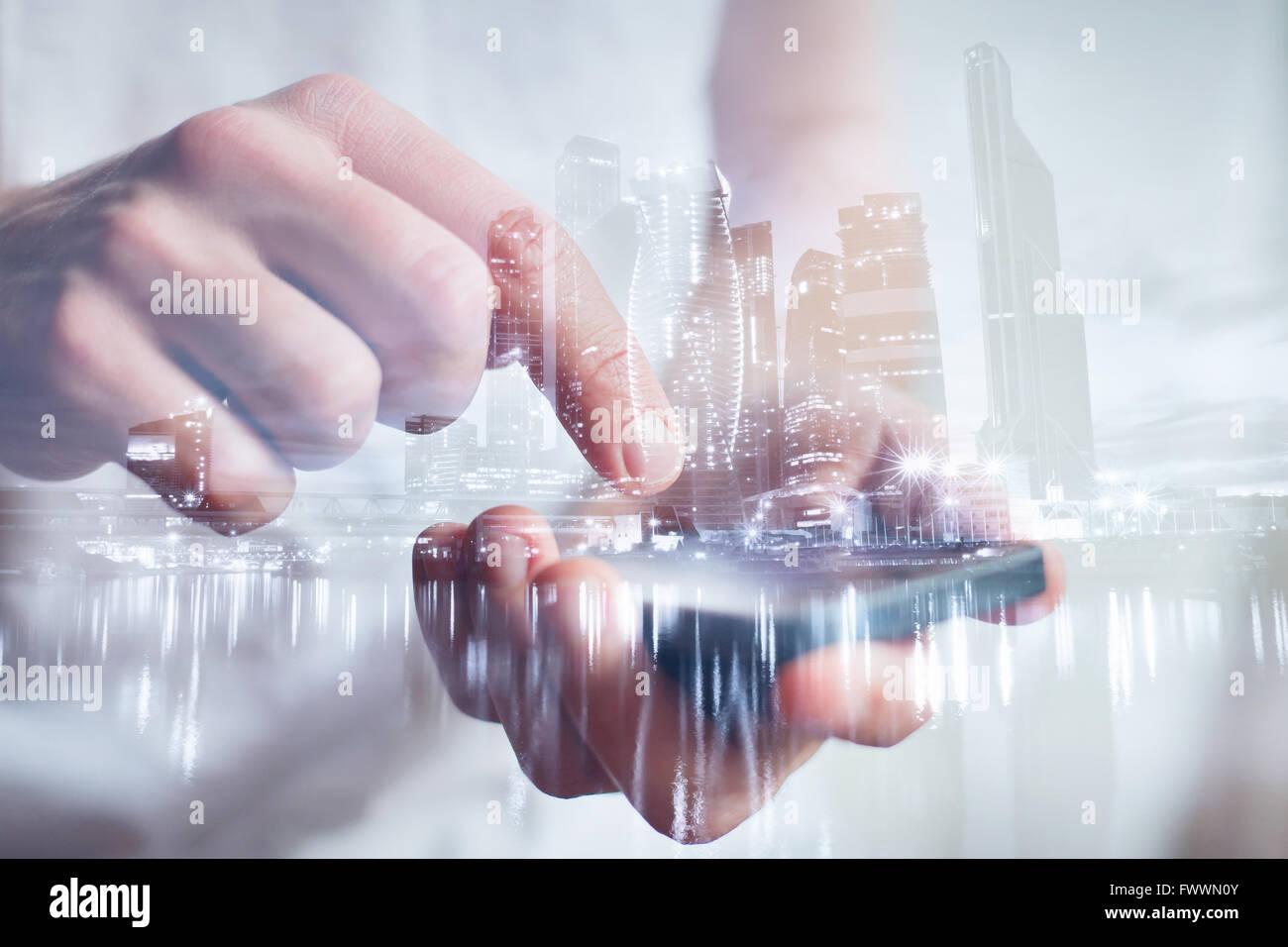 Hombre manos tocan smartphone, closeup, doble exposición con vistas al horizonte de la ciudad moderna Imagen De Stock