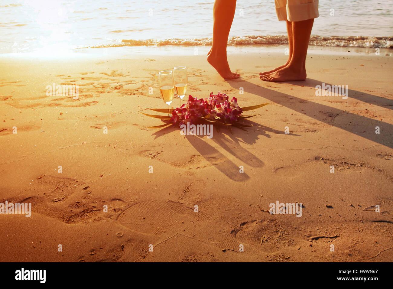 Boda en la playa, los pies de la pareja romántica y dos copas de champán al atardecer Foto de stock