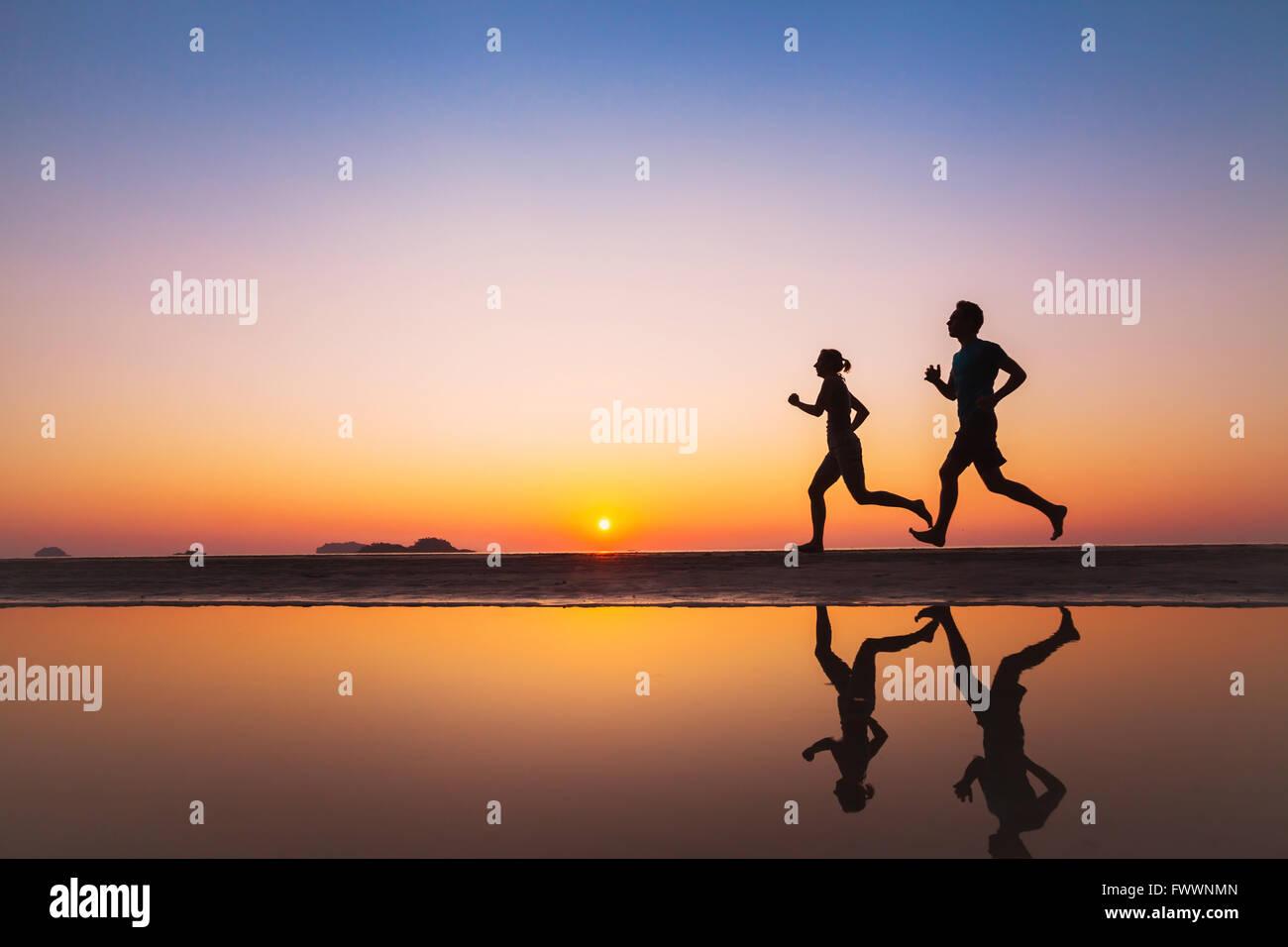 Entrenar, siluetas de dos corredores en la playa al anochecer, deporte y vida sana antecedentes Imagen De Stock