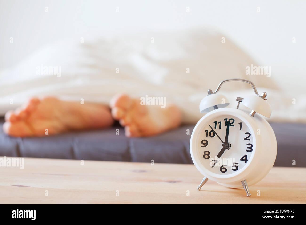 Reloj con alarma y pies de la persona que duerme, mañana concepto, wake up Imagen De Stock