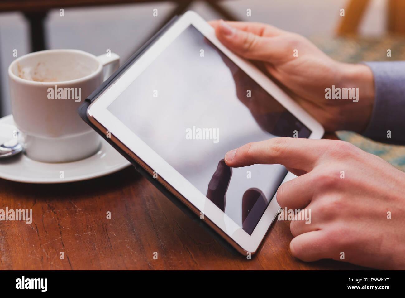 Usando internet en tablet en cafe, comprobar el correo electrónico y las redes sociales en el touchpad, acercamiento Imagen De Stock