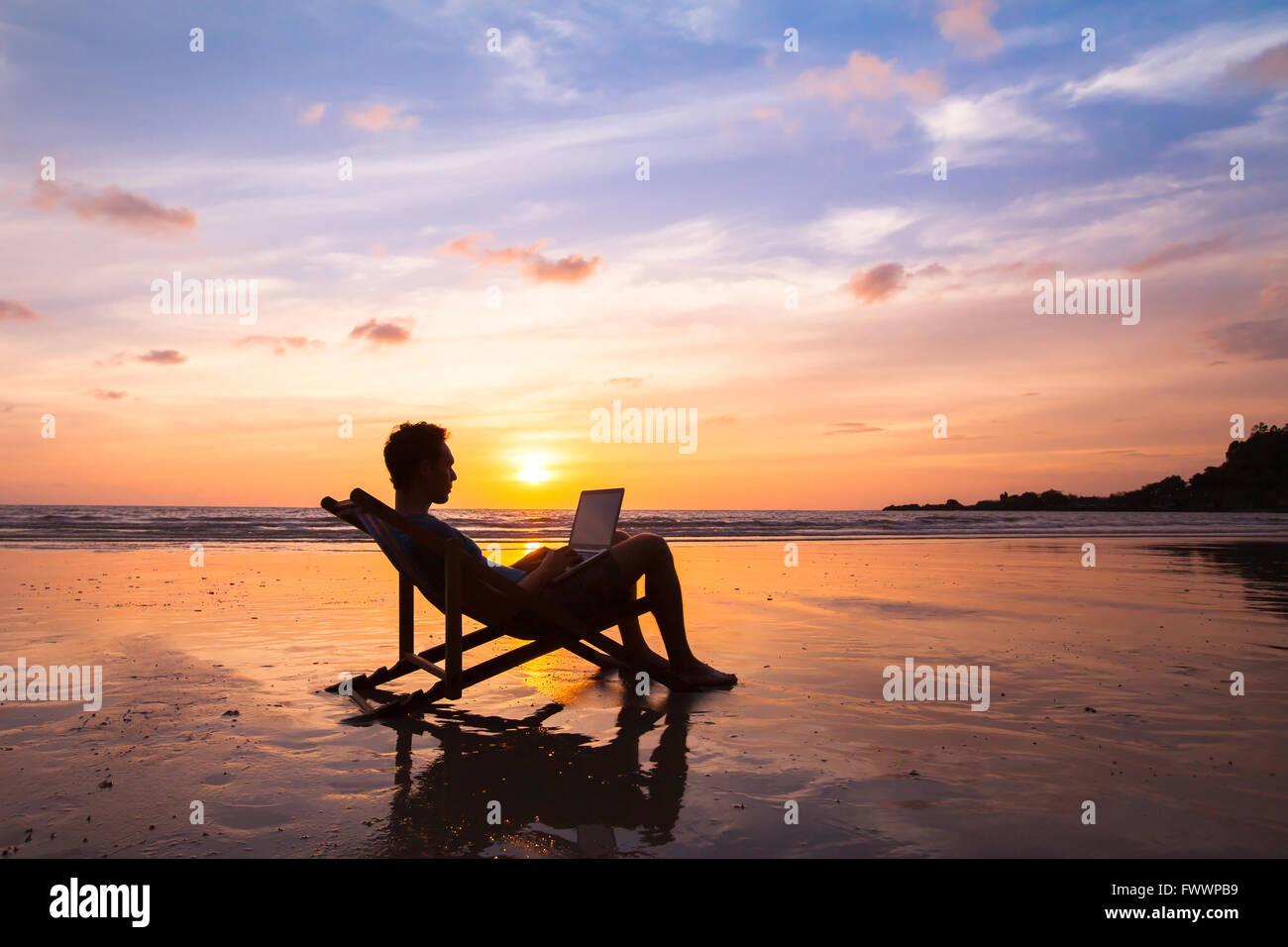 Silueta de hombre de negocios feliz con portátil trabajando en la playa Imagen De Stock