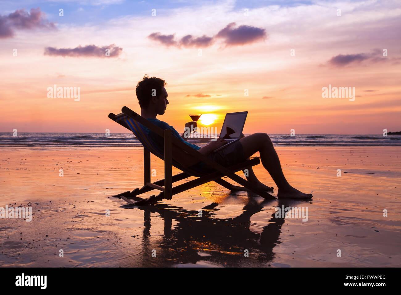 Silueta de hombre de negocios con éxito la lectura de correos electrónicos en el ordenador portátil Imagen De Stock