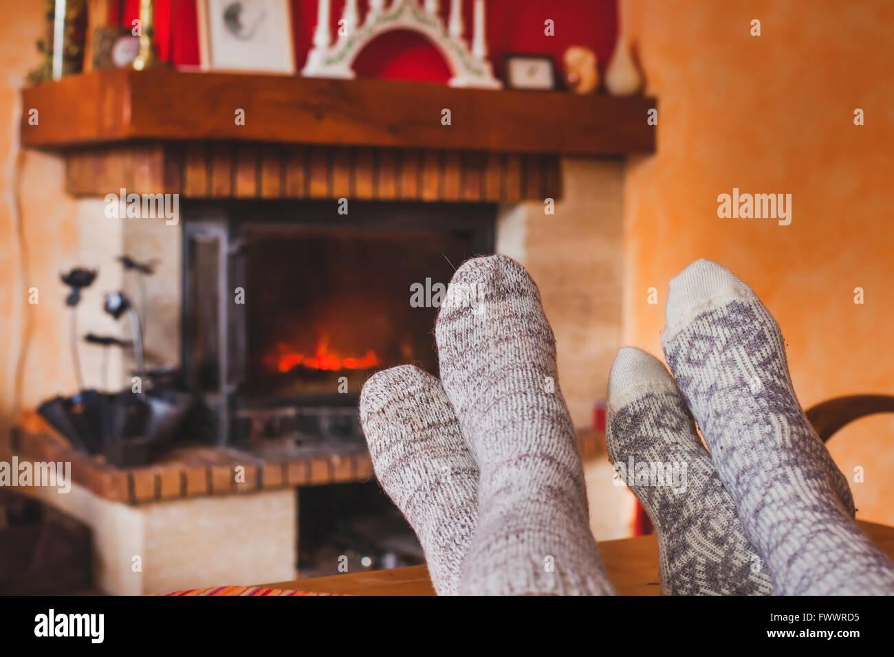 Los pies de la pareja, cerca de la acogedora chimenea en invierno, en casa de familia cerca de fuego Imagen De Stock