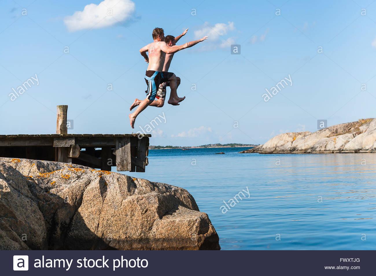 Suecia, archipiélago de Estocolmo, Uppland Vidinge, dos hombres saltar en el lago desde el embarcadero Imagen De Stock
