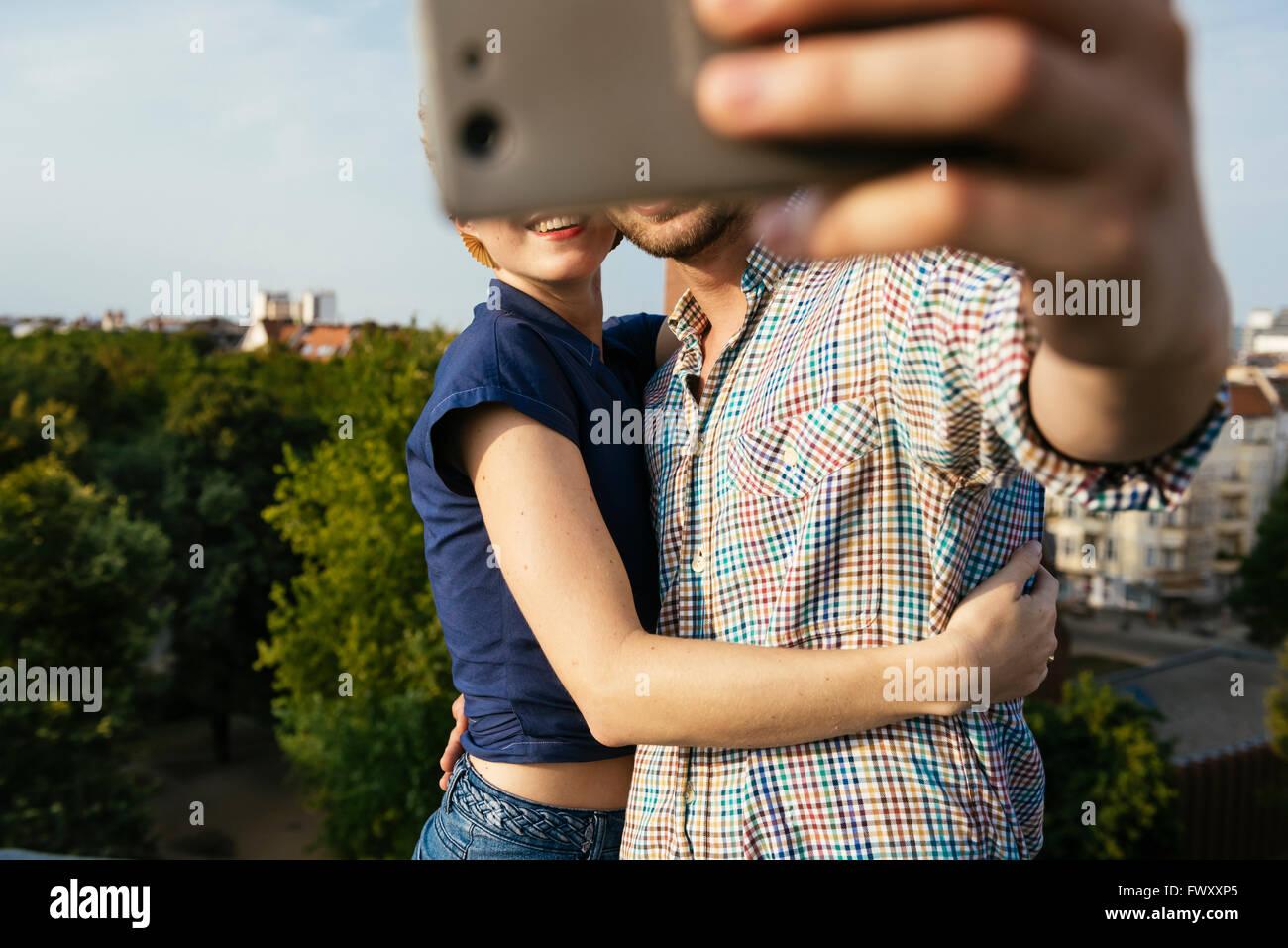 Alemania, Berlín, joven pareja abrazarse y teniendo selfie con teléfonos inteligentes.Foto de stock