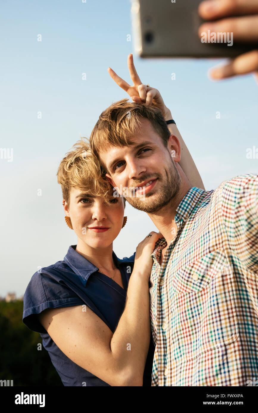 Alemania, Berlín, joven pareja abrazarse y teniendo selfie con teléfonos inteligentes. Imagen De Stock