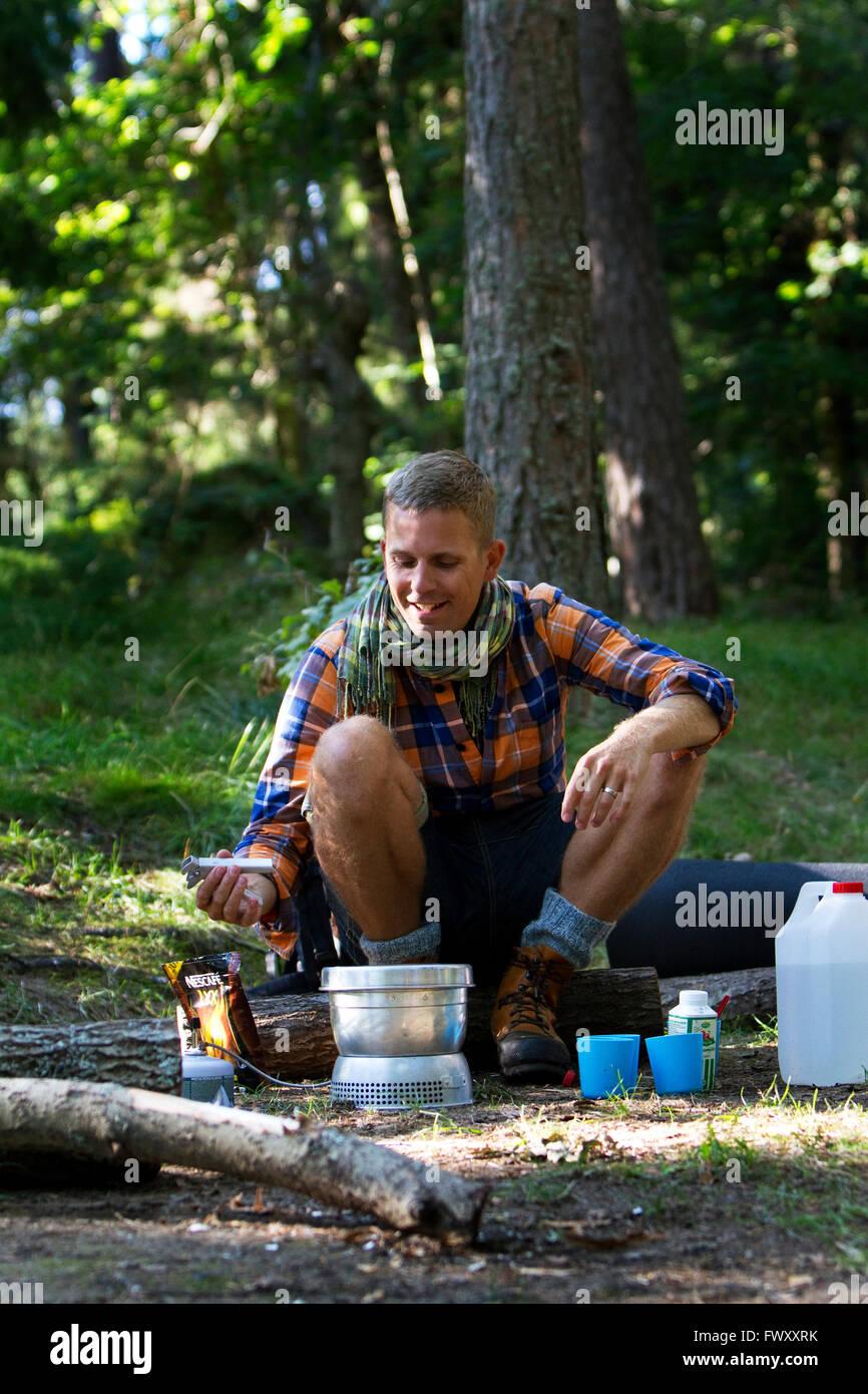 Suecia, Ostergotland, Agelsjon excursionista, preparando la comida en la estufa de camping Imagen De Stock