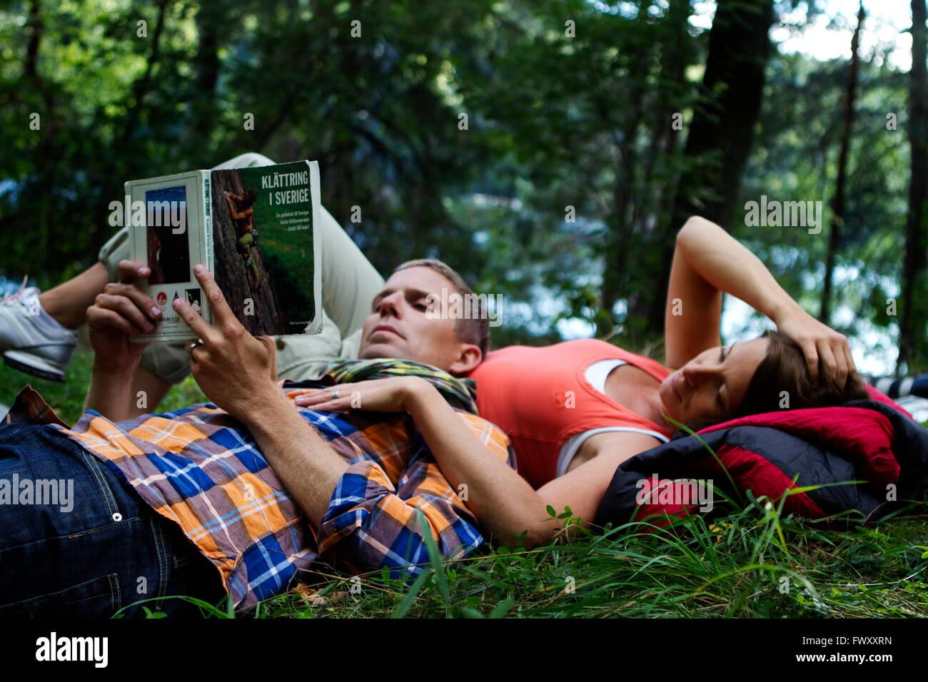 Suecia, Agelsjon Ostergotland, excursionistas, tumbado sobre el césped y leyendo la guía Imagen De Stock