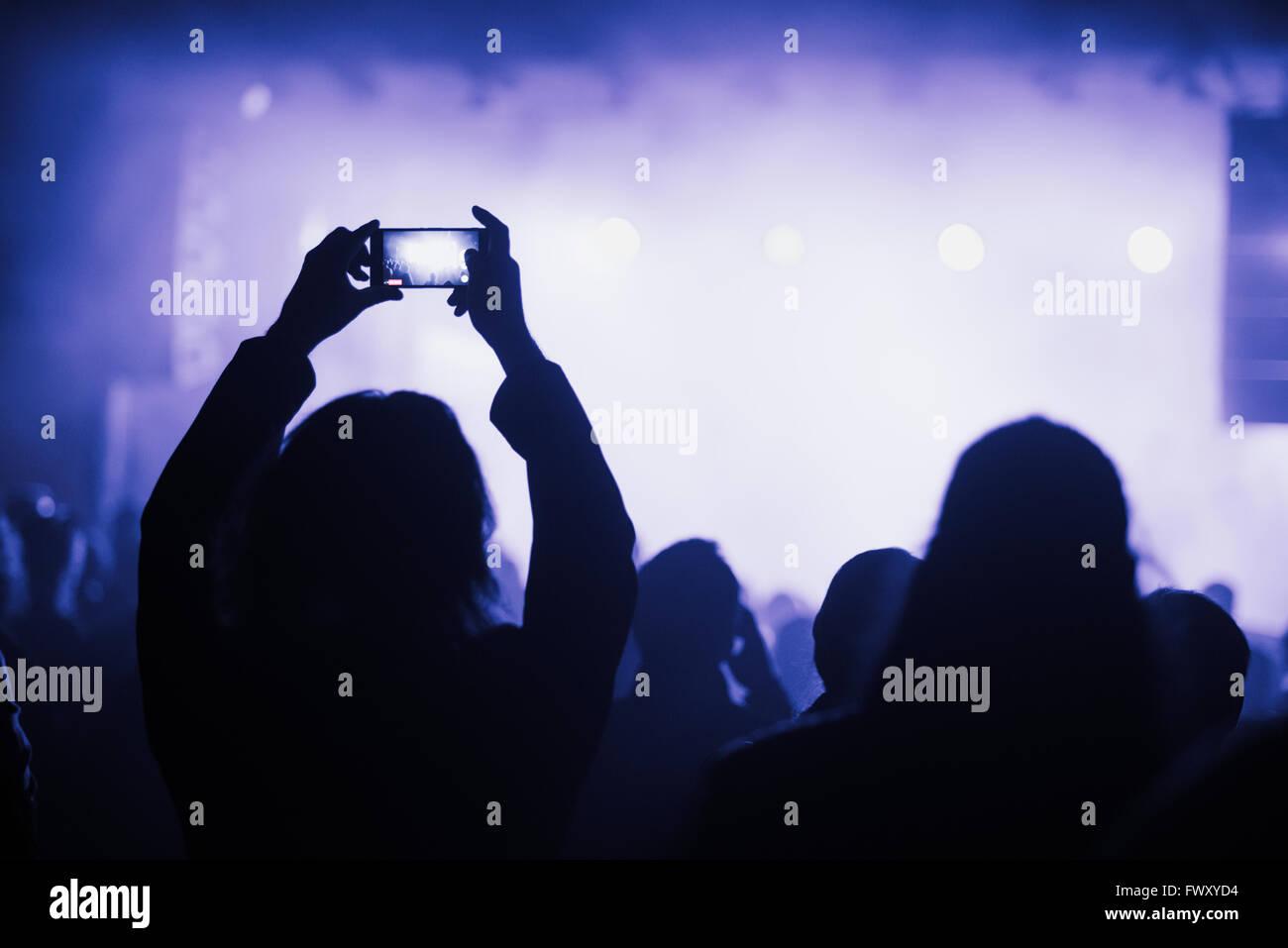 Finlandia, Helsinki, Uusimaa, Mujer utilizando smart phone en concierto Imagen De Stock