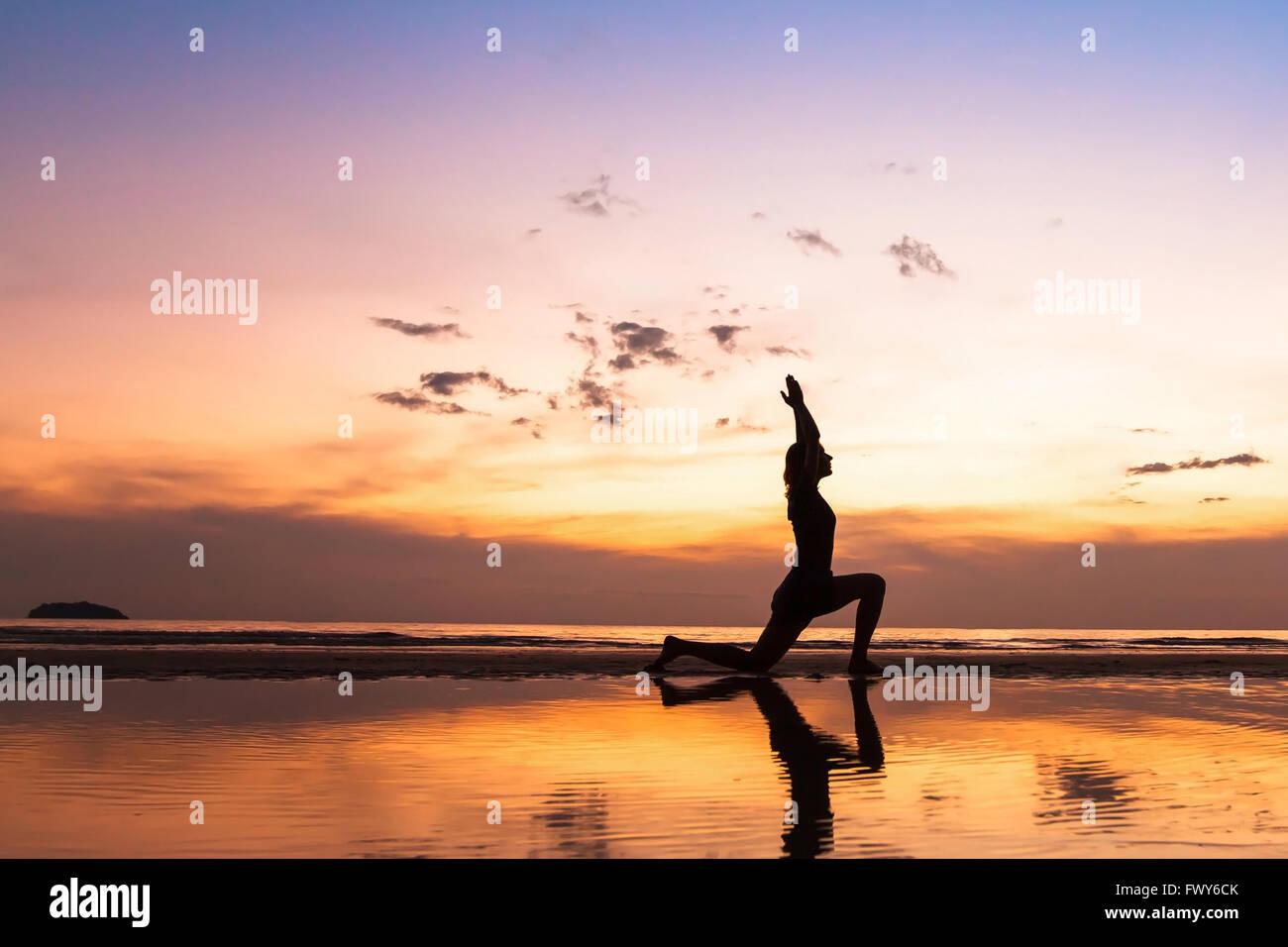 Hermoso ejercicio de yoga en la playa al atardecer, fondo con copyspace Imagen De Stock