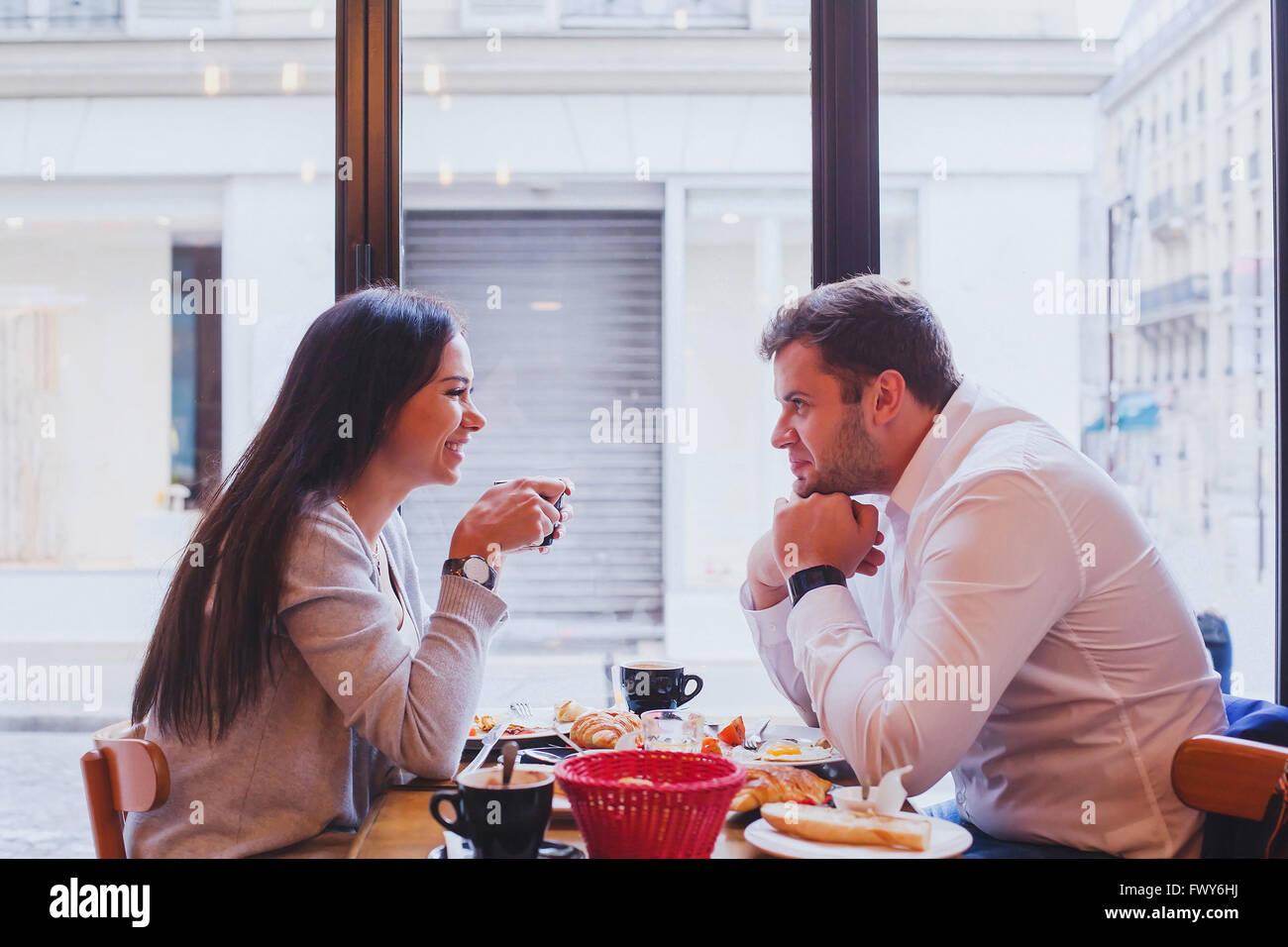 Comer en el restaurante, la feliz pareja sonriente almorzando en la cafetería, dating Foto de stock