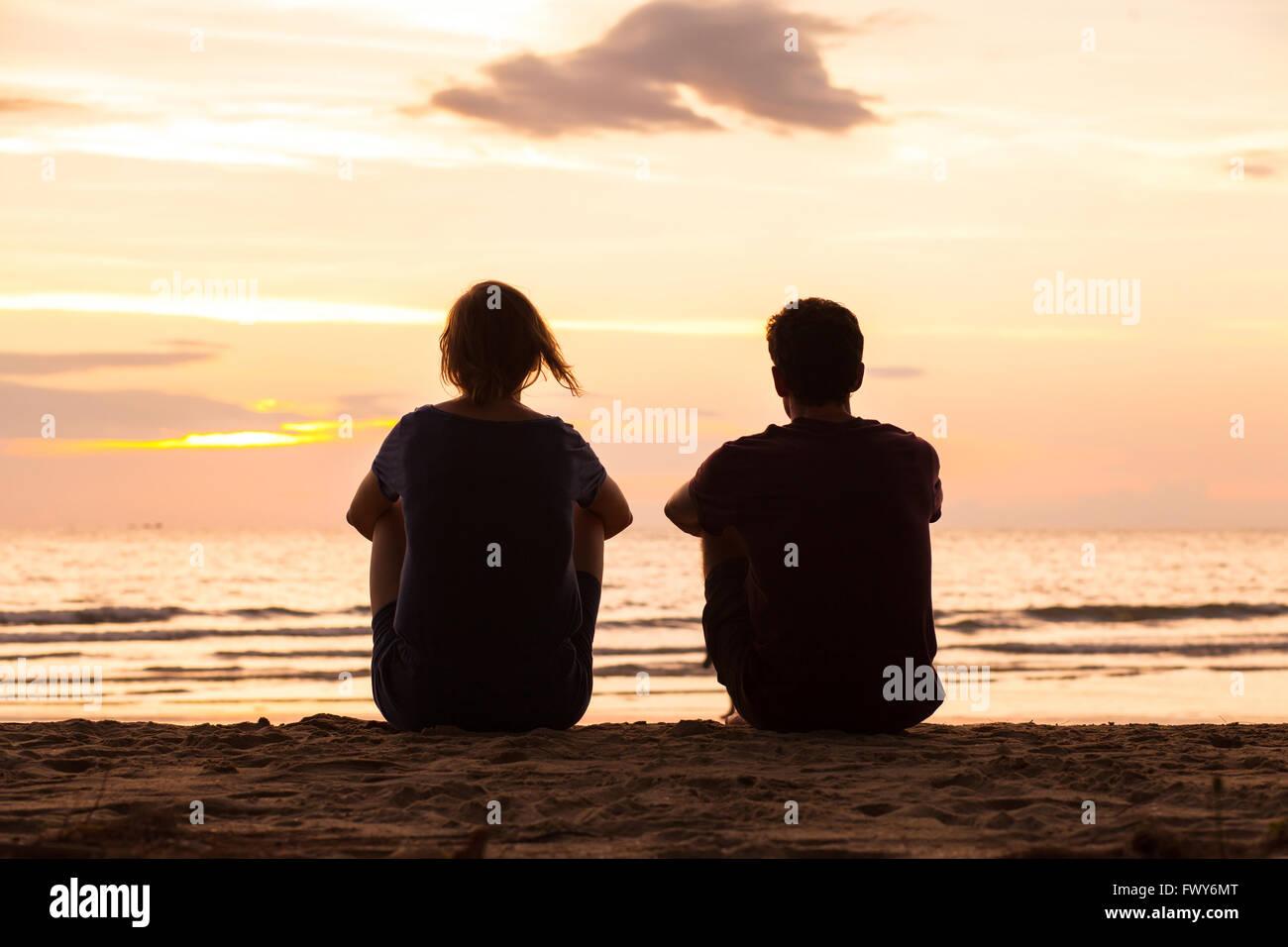 Amigos sentados juntos en la playa y observar el atardecer, concepto de amistad Imagen De Stock