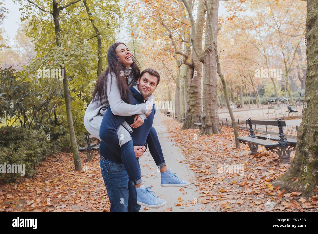 Feliz pareja joven divirtiéndose en otoño, el parque de la familia caucásica, hombre y mujer, piggyback Imagen De Stock