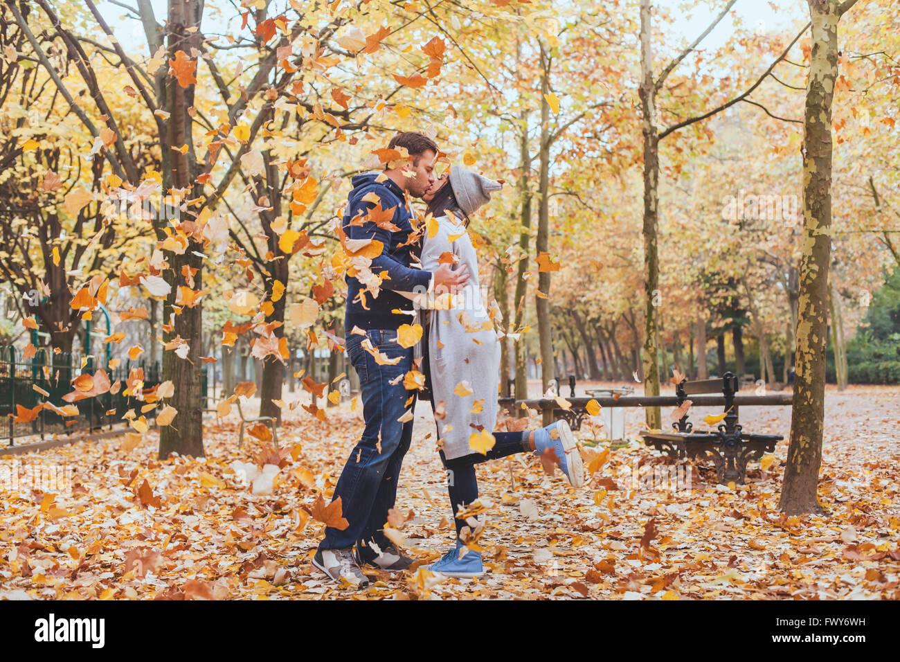 Beso de otoño, la joven pareja amorosa en el parque con la caída de las hojas Imagen De Stock