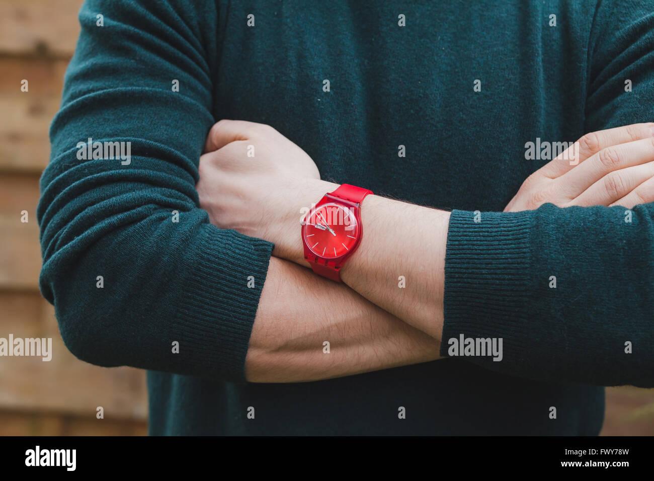 Mens moda, cerca de manos de hombres vestidos de rojo y verde reloj estilo suéter, concepto Imagen De Stock