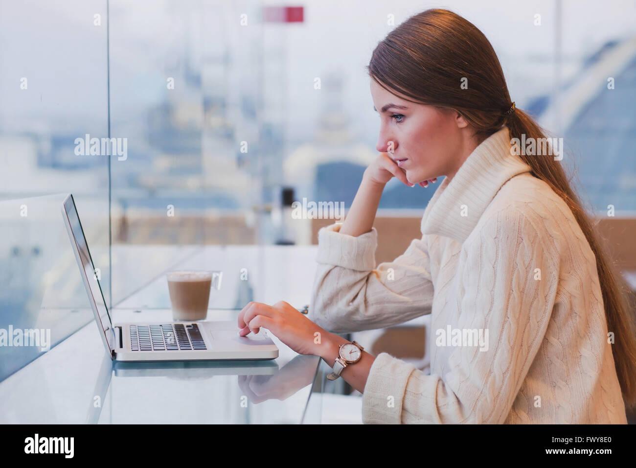 Mujer con laptop en la moderna cafetería interior, wifi gratuito, comprobar el correo electrónico Imagen De Stock