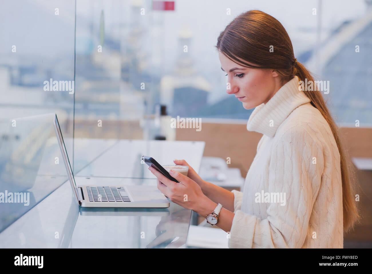 Mujer usando smart phone en la moderna cafetería inerior, aplicación móvil, comprobar el correo electrónico Imagen De Stock