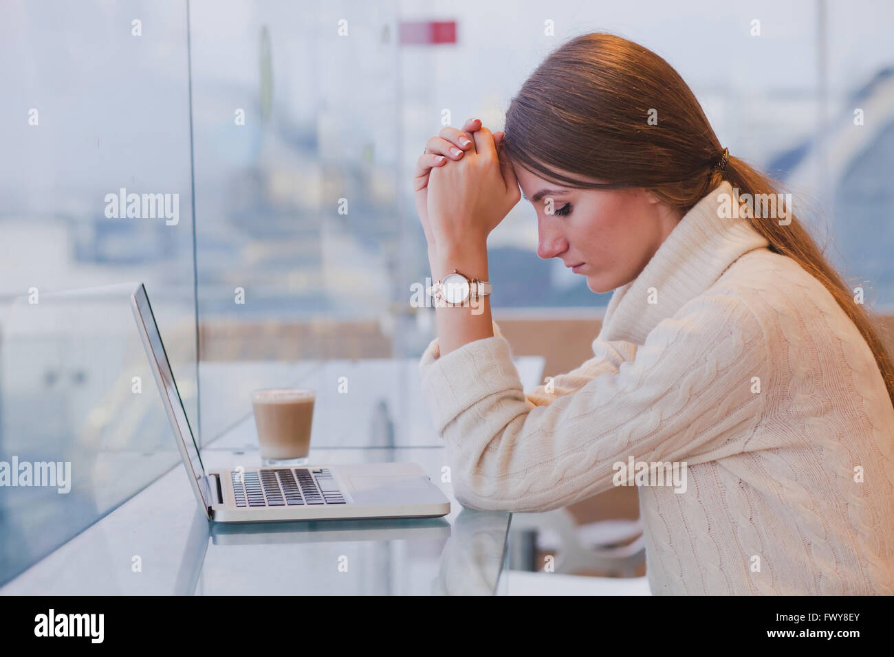 Concepto de desempleo, problema, triste cansada mujer en frente del portátil en la moderna cafetería brillante Imagen De Stock