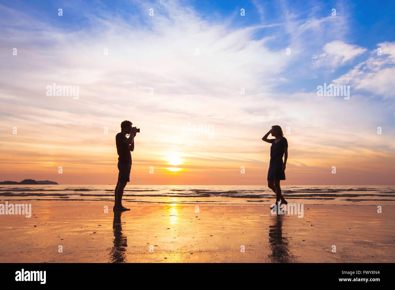 Fotógrafo y modelo, fotografías en la playa al atardecer, el hombre tomando fotos de mujer Imagen De Stock