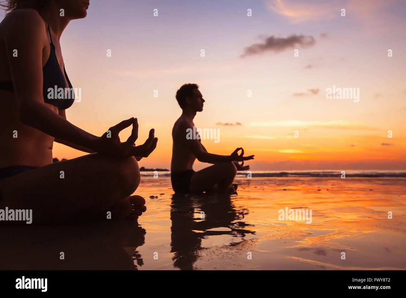Grupo de personas meditando en la playa, el yoga y la salud antecedentes Imagen De Stock