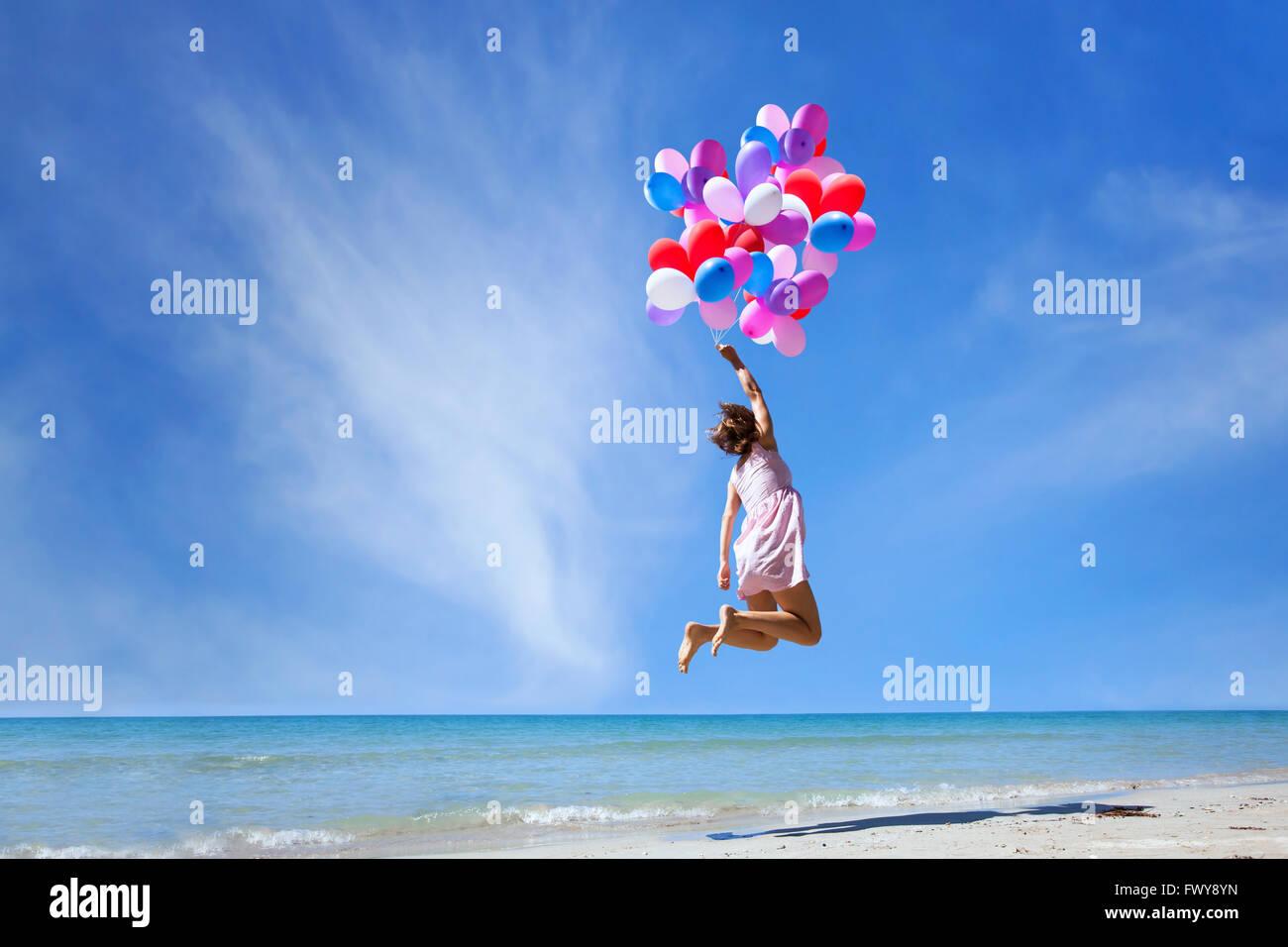 Concepto de ensueño, niña volando en globos multicolores en el cielo azul, la imaginación y la creatividad Imagen De Stock